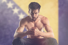 Muscular man with Bosnia and Herzegovina Flag behind Stock Photo