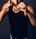 Muscular man in a boxing stance. Clenched fists stock photos