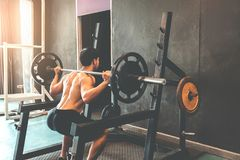 Muscular Man built athlete working out in gym and weightlifting royalty free stock image