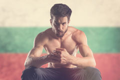 Muscular man with Bulgarian Flag behind Stock Photos