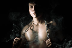 Muscular man with chain and smoke. Night in the conclusion Royalty Free Stock Photo