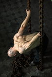 Muscular man in chains. Muscular man with bald head leaning over and pulling on chains Stock Photography