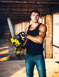 Muscular man with a chainsaw stock images