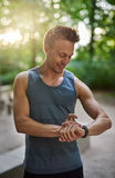 Muscular Man Checking his Watch After his Exercise. Half Body Shot of a Muscular Young Man at the Park Checking his Watch After his Exercise with Happy Facial Royalty Free Stock Images