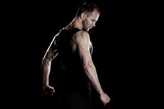 Muscular man,  clasps hands in  fist, black Stock Images