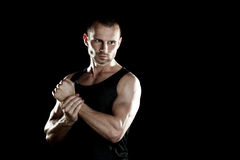 Muscular man,  clasps hands in  fist, black background, place for text on the right Stock Images