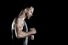 Muscular man,  clasps hands in  fist, black background, place for text on the right Stock Photography