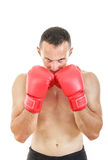 Muscular man with connected red boxing gloves near his face Royalty Free Stock Photography