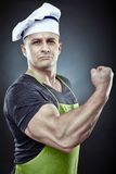 Muscular man cook displaying his biceps Royalty Free Stock Images