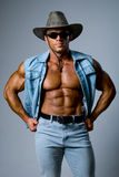 Muscular man in a cowboy hat Stock Photography