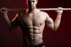 Muscular man with crossbar. One sexual strong young man with muscular body in jeans holding iron crossbar standing posing in studio on red background, horizontal stock photo