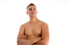 Muscular man with crossed arms looking upward Stock Photography