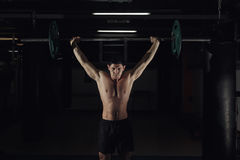Muscular man at a crossfit gym lifting a barbell. royalty free stock photo