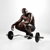 Muscular man crouching with barbell Stock Photo