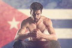 Muscular man with Cuban Flag behind. Muscular man stock photo