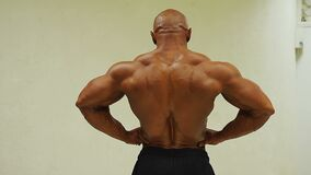 Muscular man demonstrating rear lat spread pose at sport club, bodybuilding. Stock footage stock footage