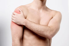 Muscular man discomfort on shoulder. Male holding his painful injured shoulder Royalty Free Stock Photography