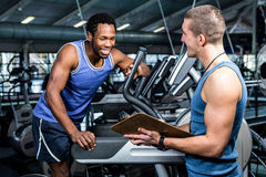 Muscular man discussing performance with trainer Stock Photography