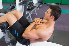 Muscular man doing abdominal crunches in gym Royalty Free Stock Photos