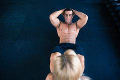 Muscular man doing abs exercise. Muscular men doing abs exercise at gym Stock Photography