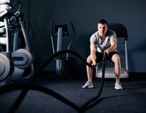 Muscular Man is Doing Battle Rope Exercise in Modern Fitness Gym. CrossFit and Healthy Lifestyle Concept. royalty free stock photography