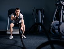 Muscular Man is Doing Battle Rope Exercise in Modern Fitness Gym. CrossFit and Healthy Lifestyle Concept. stock images