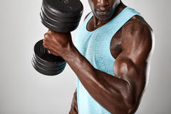 Muscular man doing biceps curl with dumbbell. Close up shot of muscular african man doing biceps curl with dumbbell against grey background Royalty Free Stock Photography