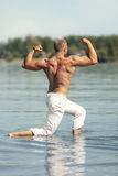 Muscular Man Doing Bodybuilding Pose in Water Royalty Free Stock Image