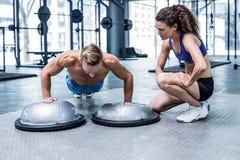 Muscular man doing bosu ball push ups Royalty Free Stock Photos