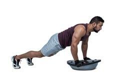 Muscular man doing bosu push ups Royalty Free Stock Photography