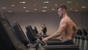 Muscular man doing cardio training on treadmill in healthy club slow motion. Athlete man running on treadmill during intensive training in fitness club stock photos