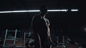 Muscular man doing crossfit training in a gym. Muscular man doing crossfit training in a dark shadowy gym lifting weights holding a barbell at waist level in a stock video