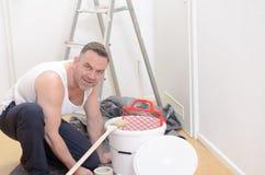 Muscular man doing DIY renovations Stock Photos
