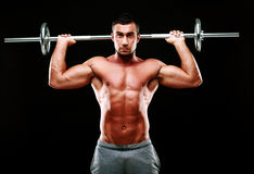 Muscular man doing exercise with barbell Stock Photography