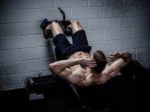 Muscular man doing exercises for abdominal in The Gym's Stock Photo