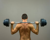 Muscular man doing exercises with barbell. Stock Image