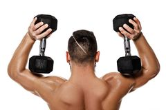 Muscular man doing exercises with dumbbells. stock photos