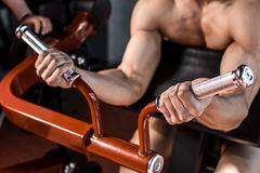 Muscular man doing exercises in the gym. Part of the body. Naked male torso. Close-up Stock Photos