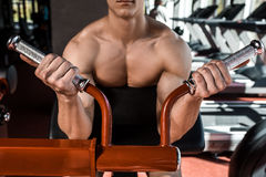 Muscular man doing exercises in the gym. Part of the body. Naked male torso. Close-up Royalty Free Stock Image
