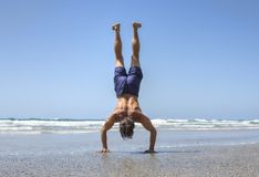 Muscular man doing handstand on beach Royalty Free Stock Photos