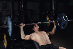 Muscular Man Doing Heavy Exercise. Athletic man pumping up muscles on bench press. Muscular Man Doing Heavy Exercise. Athletic man pumping up muscles on bench Stock Photography