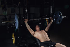 Muscular Man Doing Heavy Exercise. Athletic man pumping up muscles on bench press. Muscular Man Doing Heavy Exercise. Athletic man pumping up muscles on bench Royalty Free Stock Image