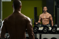 Muscular Man Doing Heavy Weight Exercise For Biceps Stock Photos