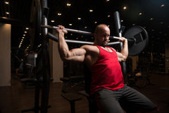 Muscular Man Doing Heavy Weight Exercise For Shoulders Stock Photo