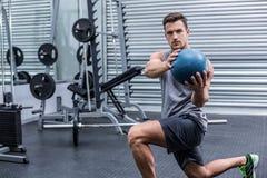 Muscular man doing medecine ball exercises. Portrait of a muscular man doing medecine ball exercises royalty free stock photo