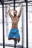 Muscular man doing pull up exercises Royalty Free Stock Image
