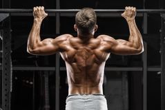 Muscular man doing pull up on horizontal bar in gym, working out. Strong fitness male showing back stock photography