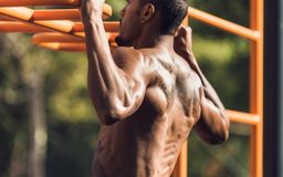 Muscular man doing pull up on horizontal bar royalty free stock photography
