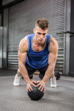 Muscular man doing pull up with medicine ball Royalty Free Stock Image