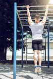 Muscular man doing pull-ups exercise outdoors. Royalty Free Stock Photo